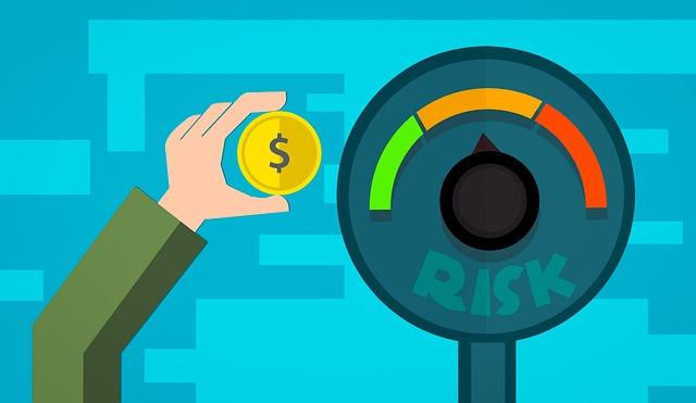"""ukazatel rizika směřující na střed """"střední rizikovosti"""" a ruka držící minci"""