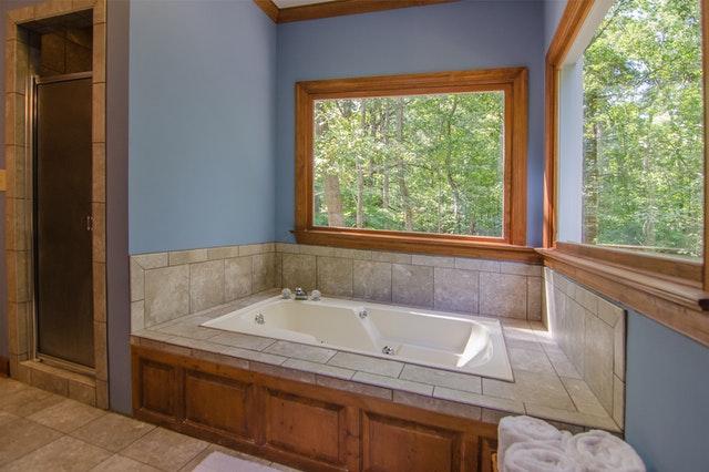 bílá vana a koupelna obložená dřevem